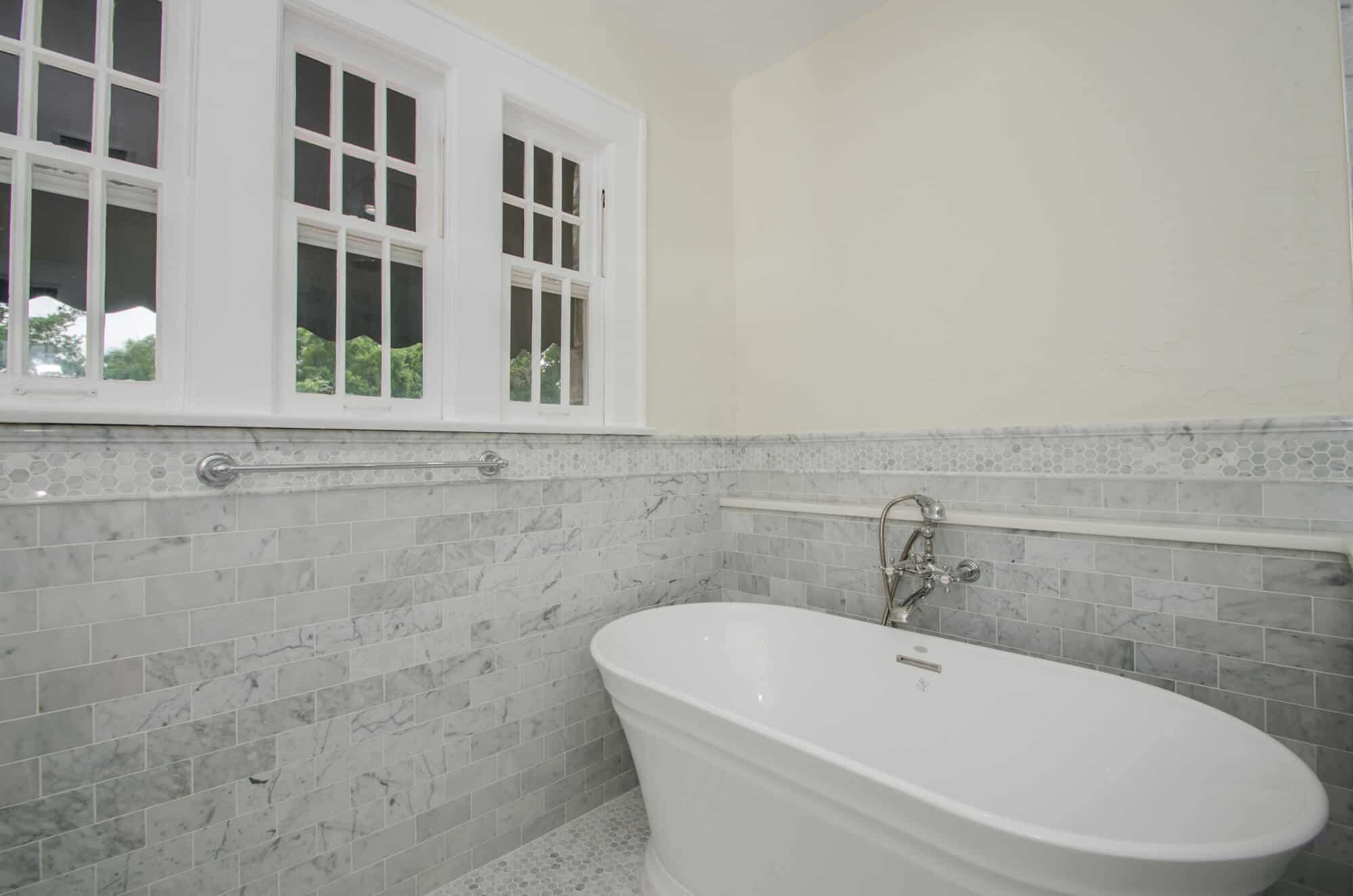 vintage style bath remodel featuring marble walls